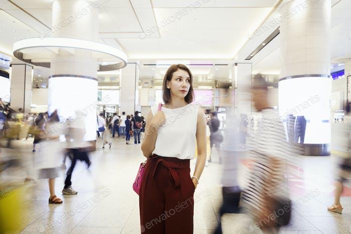 Junge Frau im Einkaufszentrum, verschwommene Bewegung der Passanten durch.
