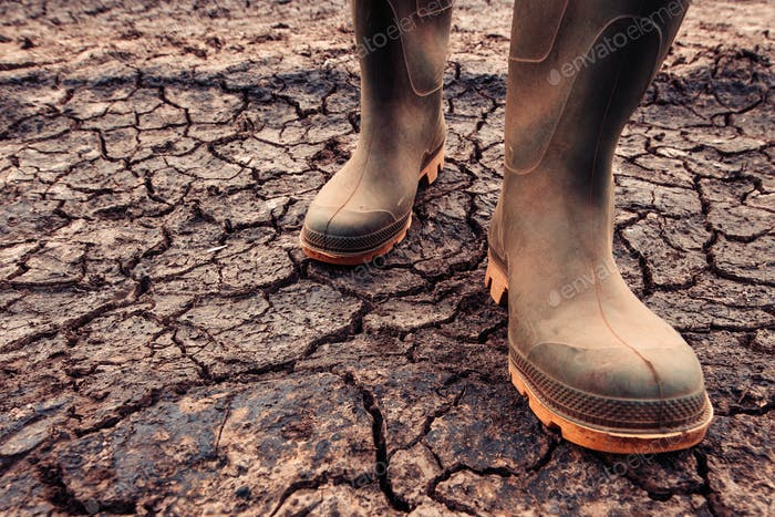 Farmer in rubber boots standing on dry soil ground