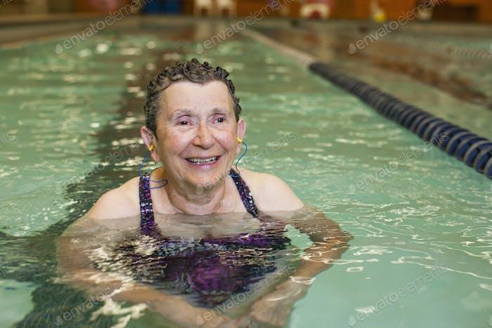 An elderly woman in a swimming pool.