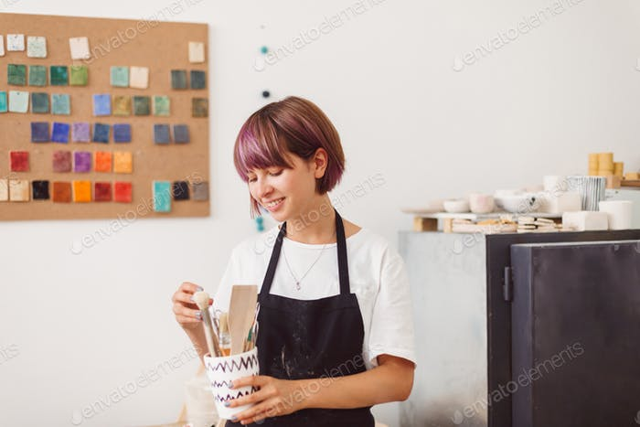 Girl with colorful hair in black apron and white T-shirt holding bowl with pottery tools in hand