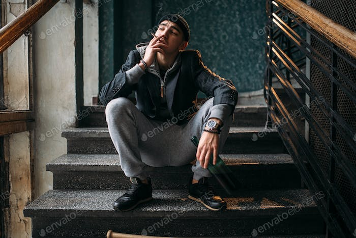 Guy with bottle sits on the stairs and smoking