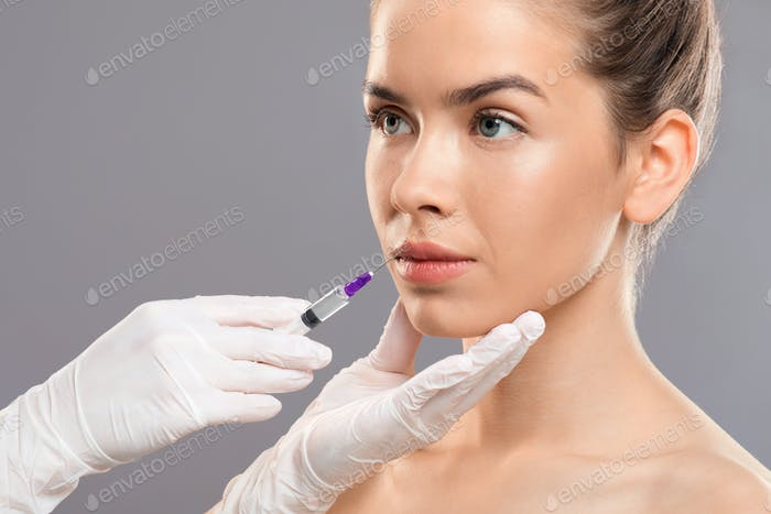 Unrecognizable cosmetitian in gloves injecting lip filler for beautiful lady