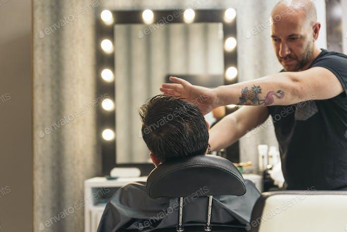 Бородатый человек, получающий бороду стрижку с бритвы Парикмахер