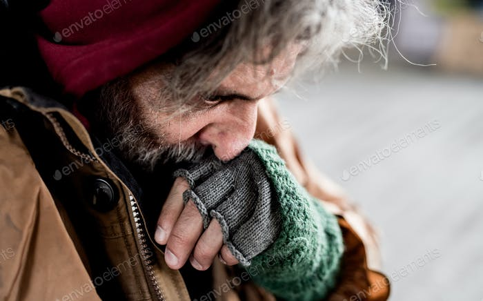 A close-up view of homeless beggar man standing outdoors in city.