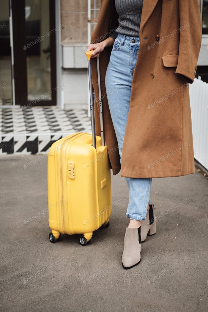 Close up casual girl in coat standing with suitcase outdoor