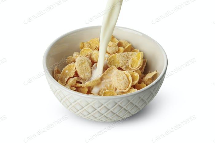 Milch wird in eine Schüssel mit Müsli gegossen, einzeln auf weißem Hintergrund