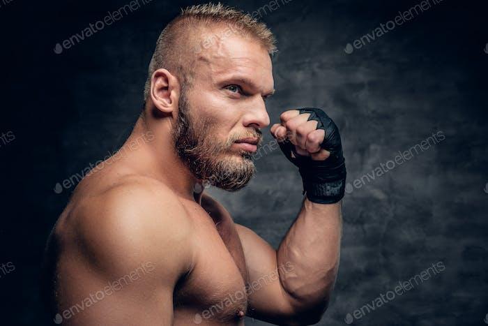 Portrait of brutal bearded fighter over dark grey background.