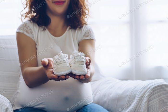 Glückliche schwangere Frau hält Babyschuhe in ihren Händen