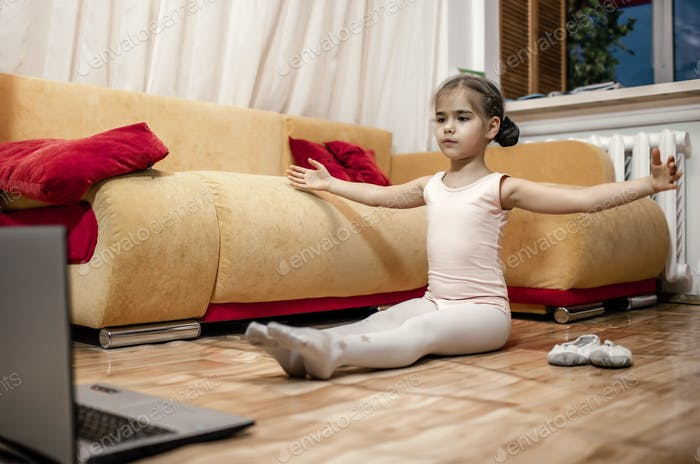 Young ballerina practicing classic choreography during online class at home, self-isolation