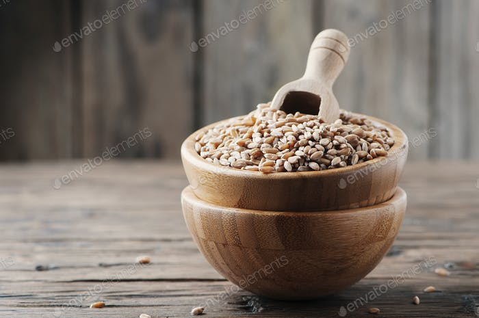 Raw pearl barley on the wooden table