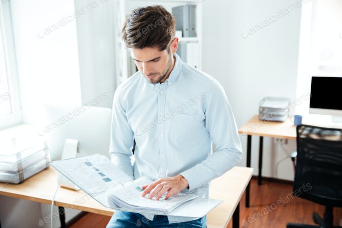 Concentrated young man holding folder with documents in office