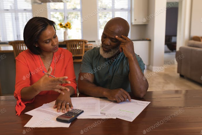 Front view of an active senior couple discussing over invoices in the living room at home