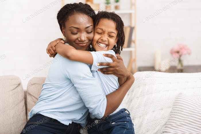 Happy black family hugging and embracing on couch