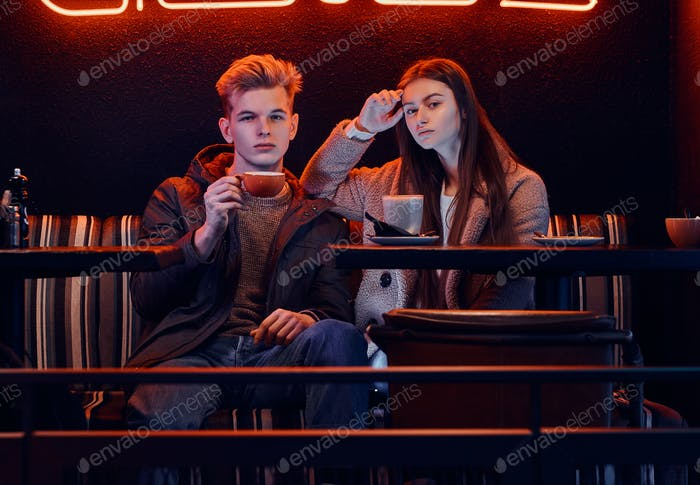 Trendy dressed young stylish couple sitting in a cafe with industrial interior