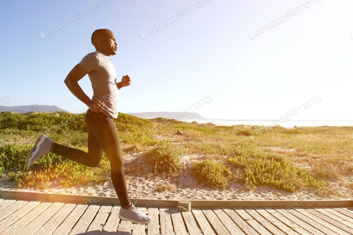 Fitness man running on the boardwalk at the beach