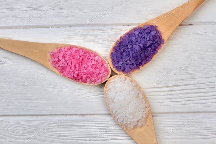 Three wooden spoons with colored salt of different color.