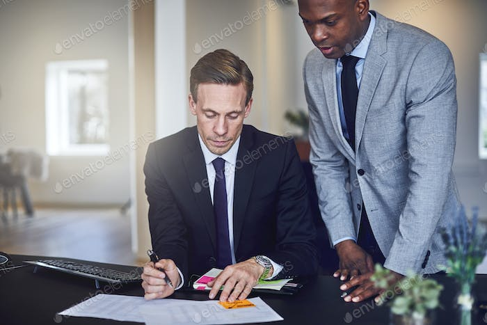 Two businessmen going over paperwork together in an office