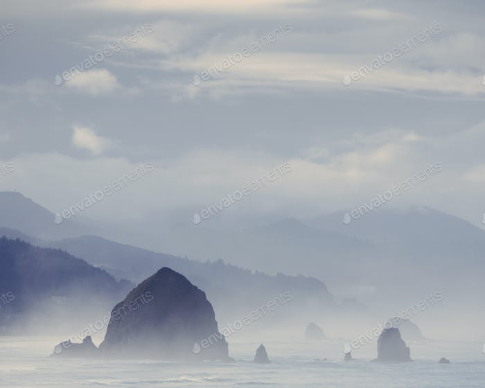 View of  Haystack Rock, at Cannon Beach and the coast of the Ecola State Park, Oregon.