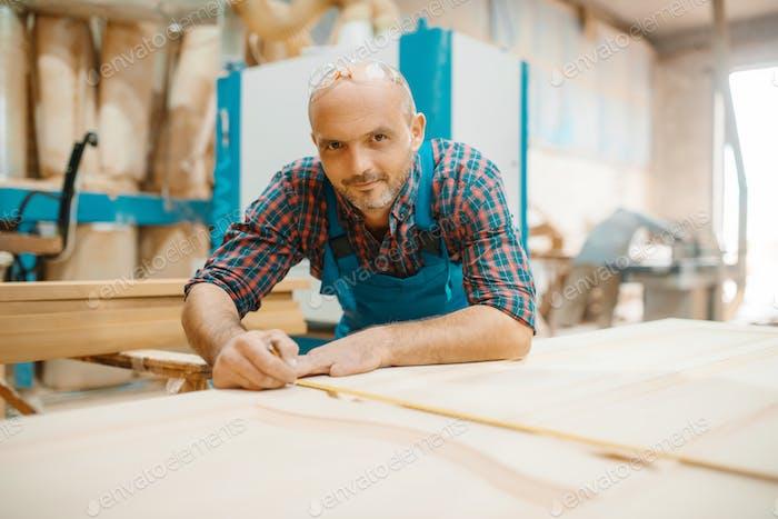 Zimmermann verarbeitet Holztür, Holzbearbeitung