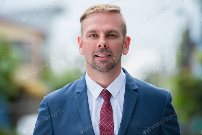 Head shot of happy businessman with blond hair smiling outdoors