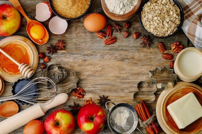 Backholz Hintergrund mit Äpfeln, Nüssen, Honig, Mehl und Butte