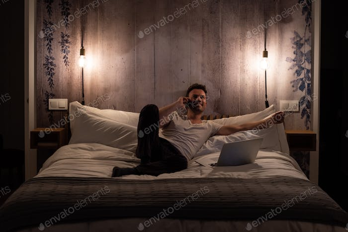 Man on the mobile phone lying down in bed