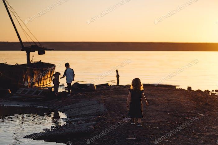 Two children walk along the beach, summer evening