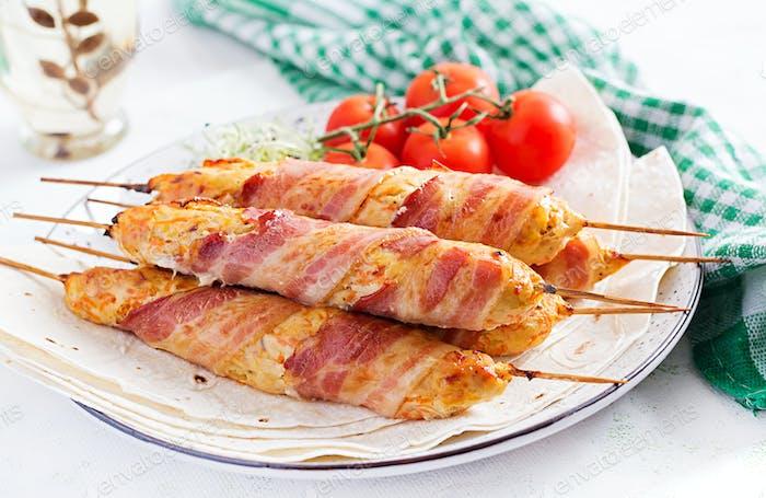Hackfleisch Lula Kebab gegrillter Truthahn (Huhn) mit Kürbis gewickelt in Speck auf Teller.