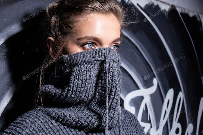 Портрет молодой модной девушки в сером свитере, стоящей ночью на улице напротив