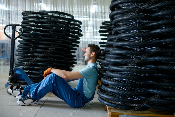 Male worker at stack of bicycle wheels on a pallet