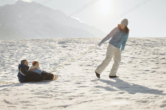 Eine Frau, die zwei Kinder auf einem Schlitten über den Schnee zieht.