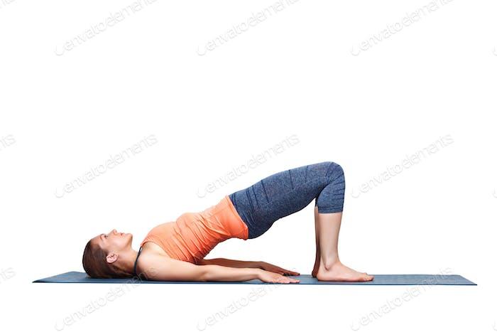 Beautiful sporty fit yogi girl practices yoga asana setu bandhasana