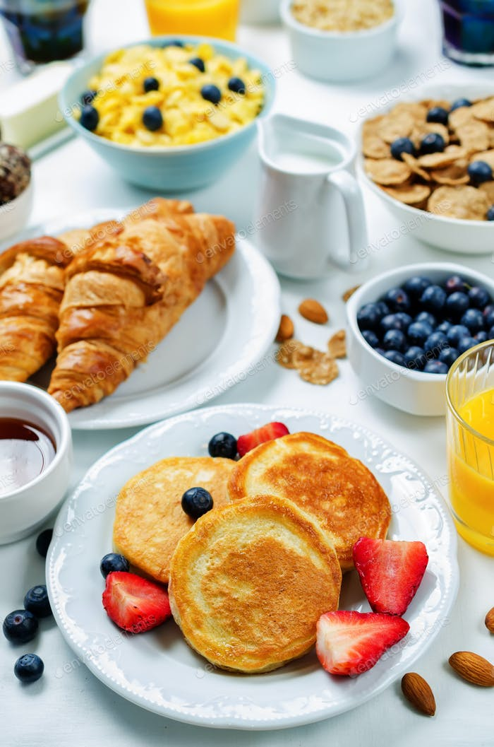 Breakfast table setting with flakes, juice, croissants, pancakes