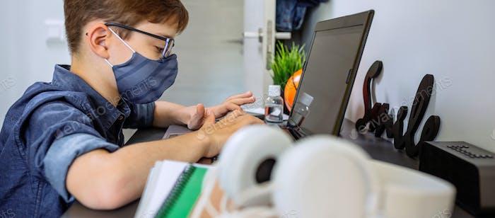 Adolescente con mascarilla haciendo la tarea con el ordenador portátil