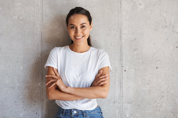 Smiling young asian woman standing with arms folded