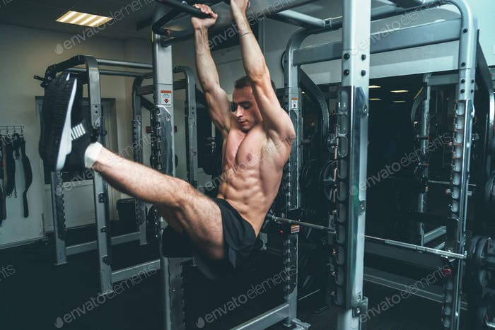 Fitness man hanging on horizontal bar performing legs raises, in the gym