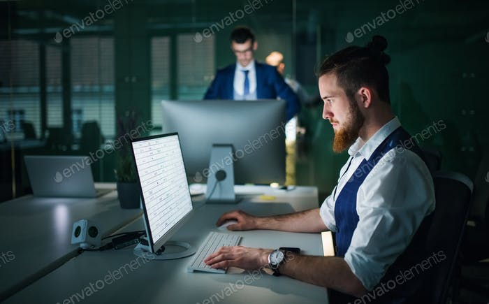 Young businessmen with desktop computer in an office, working.
