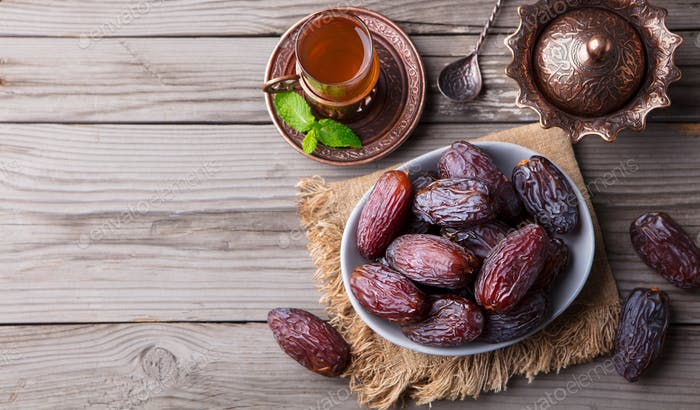 Fresh Medjool Dates in a Bowl with Tea. Ramadan Kareem. Wooden Background. Top View. Copy Space.