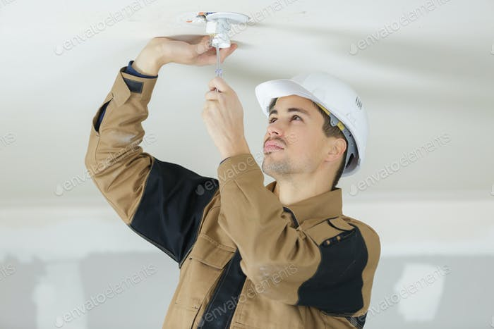 young electrician using tools for installing light