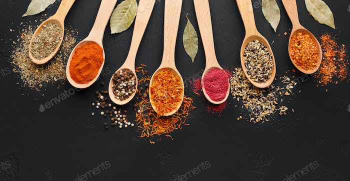 Various spices in wooden spoons on black background