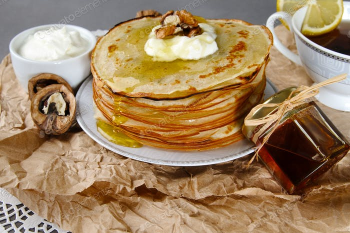 Pancakes with honey and sour cream and walnuts on a paper napkin