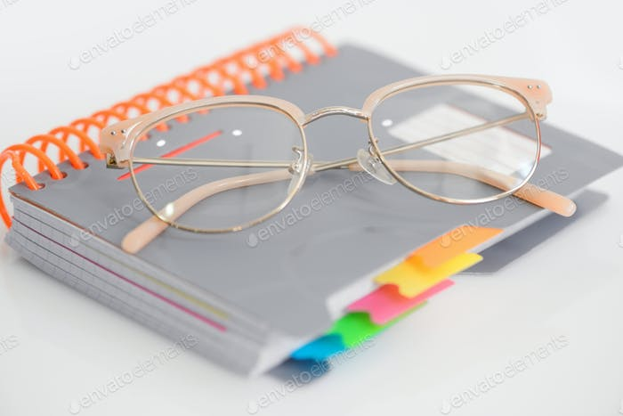 Eye glasses with spiral notebook on white background