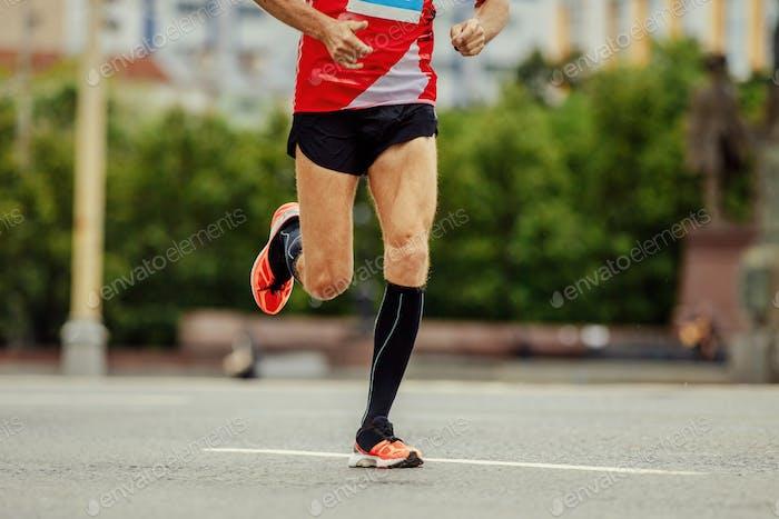 junge Läufer in schwarzen Kompressionssocken Laufen Straße in City Marathon