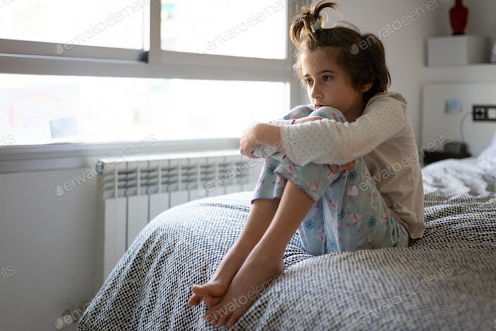 Nine-year-old girl sitting in bed bored by confinement