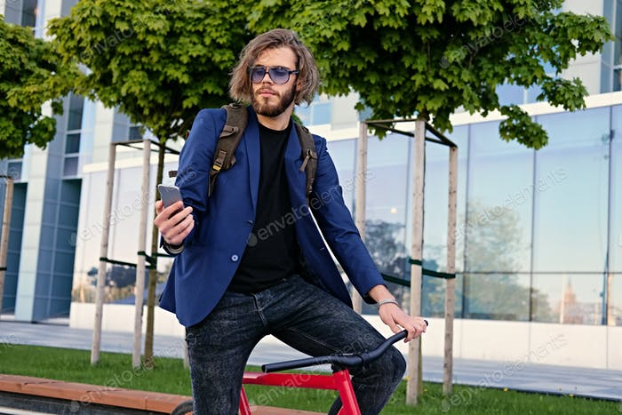 A man rides on a single speed bicycle and using a smart phone.