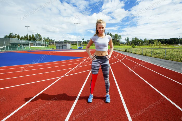 Sporty Female Standing With Hands On Hips On Running Tracks