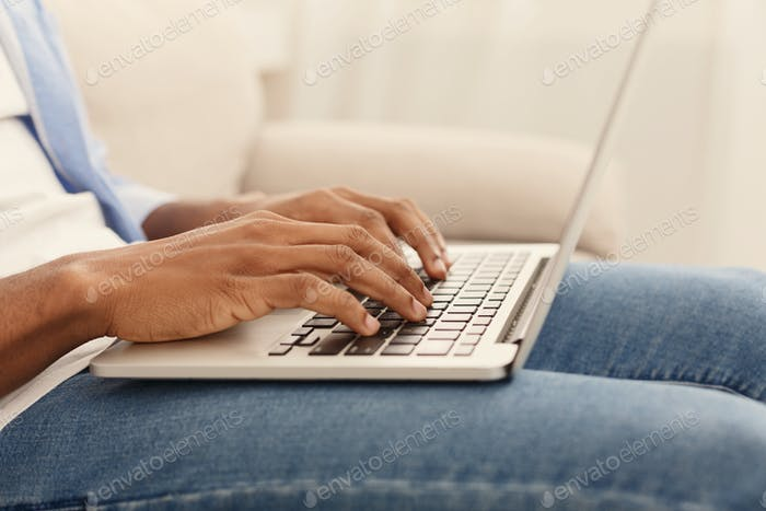 African-american guy playing video game on laptop