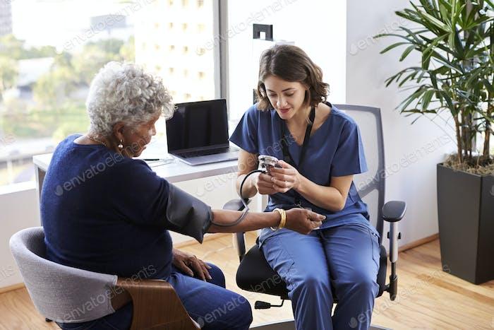 Nurse Wearing Scrubs In Office Checking Senior Female Patients Blood Pressure