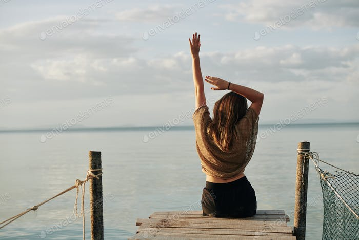 Stretching woman sitting on pier