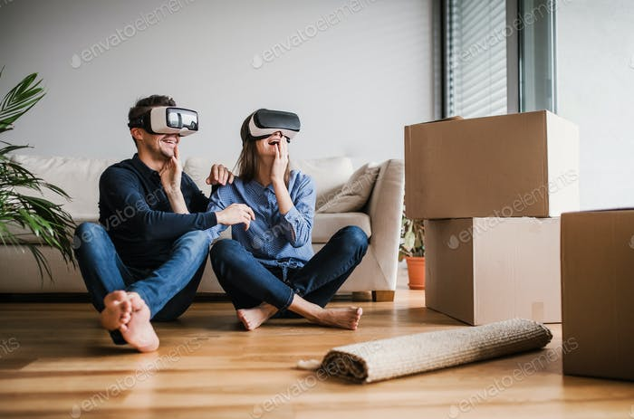 A young couple with VR goggles sitting on a floor, moving in a new home.
